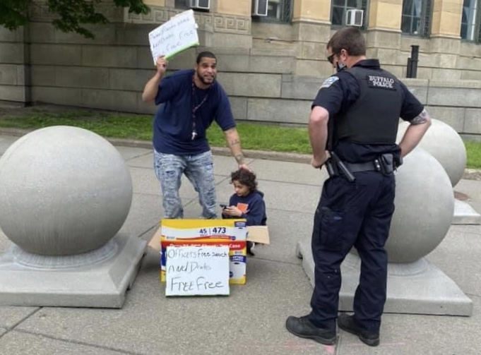 Father and son hand out drinks and snacks to police officers outside City Hall after riots